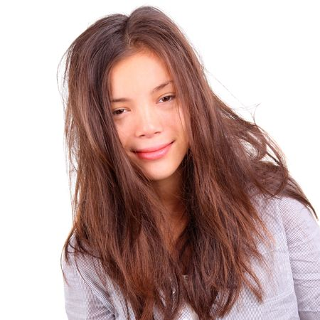 messed: Tired woman portrait. Tired woman with very messy long morning hair and a silly smile - just out of bed. Beautiful mixed asian  caucasian model isolated on white background.