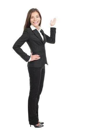 Businesswoman showing / pointing at copy space in full length. Confident mixed race chinese / caucasian woman isolated on white background.  Stock Photo - 6284041