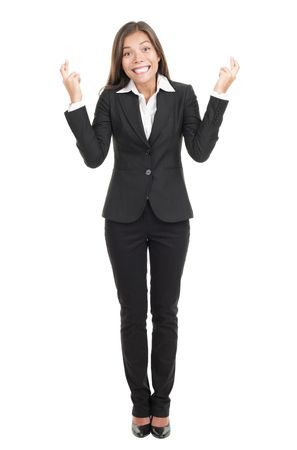 Businesswoman crossing fingers hoping for the best. Attractive mixed race chinese  caucasian woman isolated on white background in full length. photo