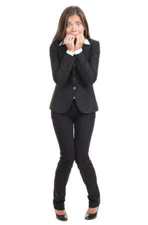 Nervous scared woman biting her nails. Funny asian businesswoman isolated in full length on white background. Mixed caucasian  chinese model.