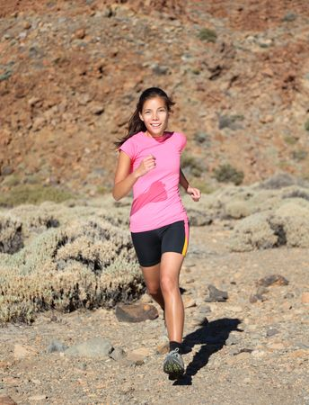Woman running. Female trail runner running on volcano. Beautiful mixed race chinese / caucasian. Stock Photo - 6538287