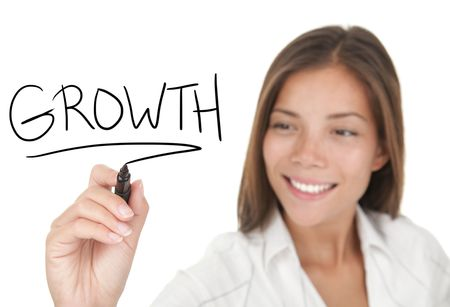Growth and success in business concept. Young beautiful businesswoman with pen writing growth on whiteboard. Focus on the black marker. Mixed race Chinese / Caucasian model isolated on white background.
