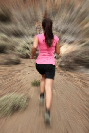 Running - woman runner in motion zoom blur for speed effect. Female running outside in desert. photo