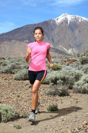 Running. Cross-country trail runner. Woman running  jogging on the mountain  volcano Teide on Tenerife. Beautiful mixed chinese asian and caucasian female model. photo
