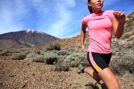 Running. Woman Cross country trail runner running on the mountain / volcano Teide on Tenerife. Beautiful mixed chinese asian / caucasian female model. 스톡 콘텐츠
