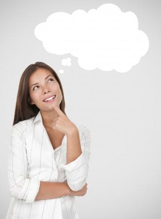 Mujer de pensamiento pensativa. Incluyendo la burbuja de pensamiento con el espacio de la copia en fondo gris.