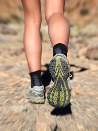 training shoes: Woman running on trail in desert. Zoom motion blurred closeup shoes of woman trail running in desert.