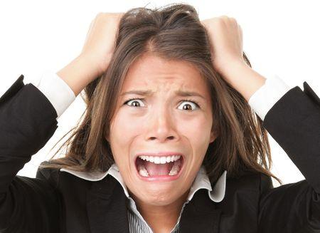 行き: ストレス。重点を置かれる女性の欲求不満で彼女の髪を引っ張って狂った起こっています。白の若い実業家のクローズ アップ。 写真素材