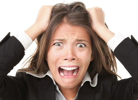 going crazy: Stress. Woman stressed is going crazy pulling her hair in frustration. Close-up of young businesswoman on white.