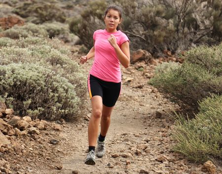 Woman running. Woman trail running outdoors on dirt single track in desert landscape in cross country running shoes. 스톡 콘텐츠