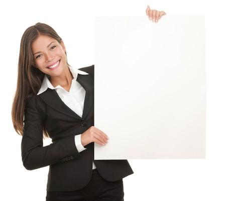 businesswoman suit: Signo de la pizarra en blanco de explotaci�n empresaria. Mujer de negocios casual en traje es celebrar el letrero de la revista billboard en blanco y mostrando su copia-espacio vac�o. Aislado sobre fondo blanco. Foto de archivo