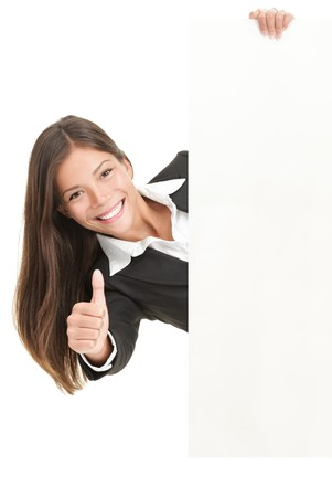 thumb's up: Advertisement woman holding sign. Businesswoman in suit giving the thumbs up success sign while showing a blank white billboard sign. Mixed race Chinese Asian  Caucasian woman isolated on white background.