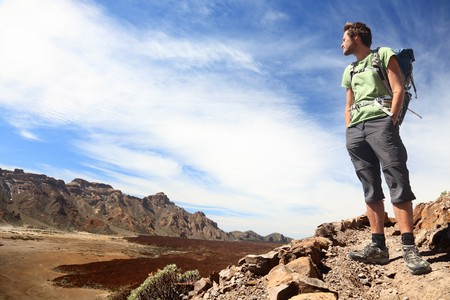 Hiker looking at view / copyspace during a hiking trip in beautiful volcano landscape on Teide, Tenerife.