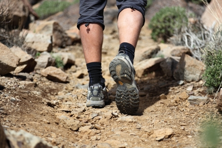 hiking shoes in action on a mountain desert trail path. Close-up of male hikers shoes. Photo is from Tenerife.  Stock Photo - 6988903