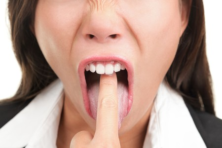 Business woman annoyed, frustrated and fed up sticking her finger in her throat showing she is about to throw up.  photo