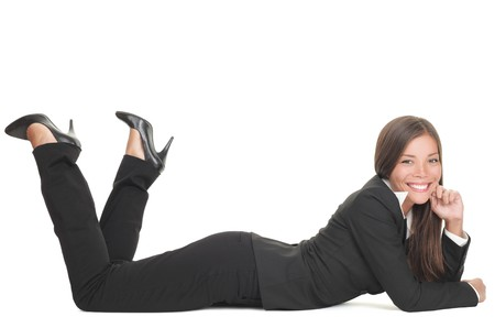 lying down on floor: Business woman lying down on floor isolated on white smiling looking at camera. Young mixed race Chinese Asian Caucasian businesswoman.