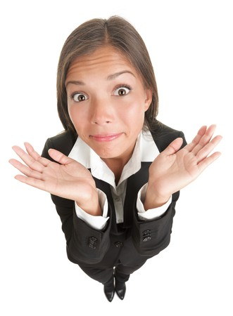 hand on shoulder: Funny Businesswoman shrugging isolated on white. Asian-Caucasian young woman with her palms out showing doubt in a full length isolation from a high angle view. Stock Photo
