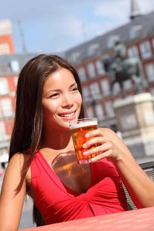 Woman drinking beer on cafe outside in Madrid, Plaza Mayor. The famous square with tourist attraction, statue of Felipe III is in the background. Stock Photo
