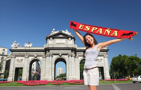 tourist destination: Spain - Madrid Tourist holding Espana banner in front of Puerta de Alaca on Plaza de la Independencia - famous tourist attraction.