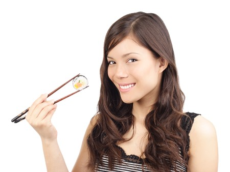 Sushi woman holding sushi with chopsticks looking at the camera smiling. Isolated on white background, Asian  Caucasian model. photo