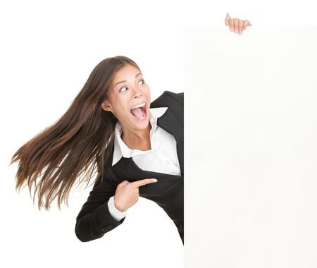 donna entusiasta: Donna segno vuoto. Businesswoman eccitata che punta poster cartellone vuota. Young business woman mista etnica indoeuropea asiatico. Isolato su sfondo bianco.
