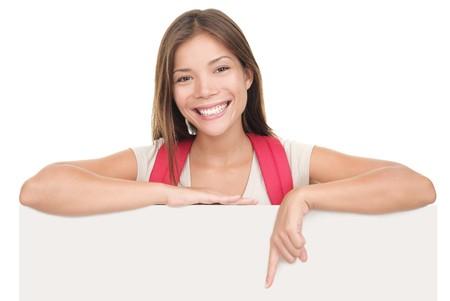 ragazza che indica: Universit� femminile  studente di college in piedi sopra segno di vuoto vuoto cartellone isolato su sfondo bianco. Giovane donna asiatica  Caucasian studente.