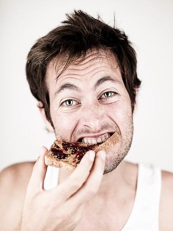 jelly sandwich: Man eating breakfast toast with peanut butter and jelly. Stock Photo