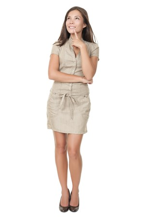 full length: Thinking woman standing in full length isolated on white background in beige neutral dress. Mixed asian  caucasian young woman.