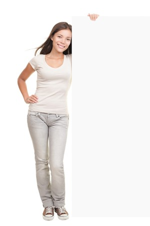 Woman showing billboard banner - white and blank with copy space. Caucasian asian model isolated on white background in full length. photo