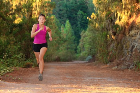 Female athlete running on forest road - copy space. Chinese Asian  Caucasian female woman runner. photo