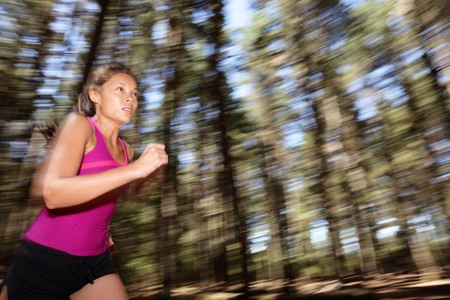 Running, Female runner running fast at great speed in forest. Mot�on blurred image of beautiful Asian  Caucasian woman athlete sprinting outdoors in tank top. photo