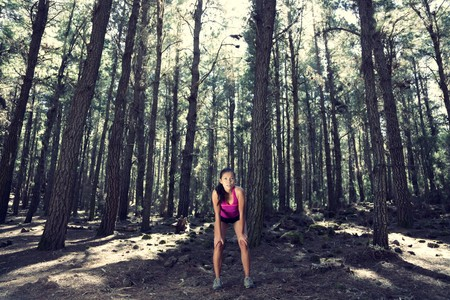 Runner relaxing after running in atmospheric enchanted forest. Beautiful woman model.  photo