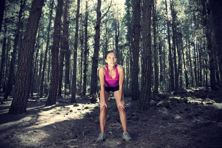 Woman running in forest. Female runner taking a break from running in beautiful forest with lots of mood  atmosphere and copy space. Beautiful young female athlete.  photo