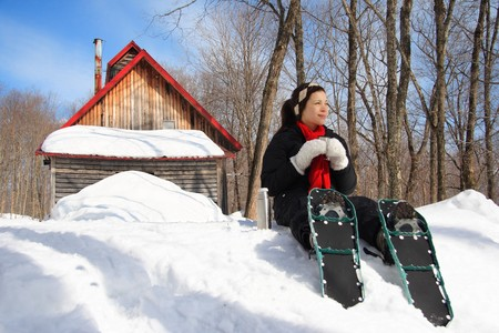 Snowshoeing in winter. Woman on snowshoes resting from hiking in beautiful winter forest. Cabin in the background. From Quebec, Canada. photo