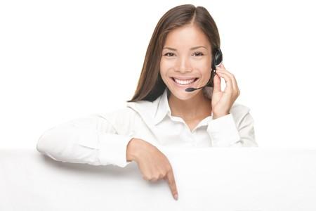 servicio al cliente: Mujer de servicio al cliente con auriculares mostrando y apuntando a la bandera de signo de billboard en blanco, joven sonriente China modelo femenino del C�ucaso y Asia.  Foto de archivo