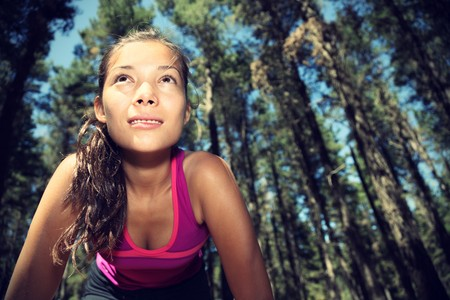 Runner. Woman running in forest taking a break from working out. Beautiful young female athlete - copy space. photo