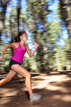Runner, Female running fast in forest. Motion blurred image of beautiful Asian  Caucasian woman athlete sprinting outdoors in tank top - copy space. photo