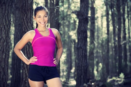 Woman runner in forest. Portrait of female runner taking a break from running in beautiful forest with lots of mood  atmosphere and copy space. Beautiful young female athlete.  photo