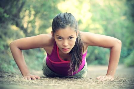 Oefening vrouw doet push-ups buiten in het bos, mooie jonge vrouwelijke atleet.