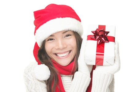 Santa woman showing gift wearing Santa hat. Christmas woman portrait of a cute, beautiful smiling mixed Asian  Caucasian model. Isolated on white background.  photo
