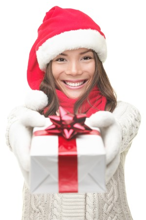 Christmas gift woman smiling holding present isolated on white background. Santa girl in winter sweater showing gift wearing Santa hat. Cute, beautiful model: mixed Asian  Caucasian. photo