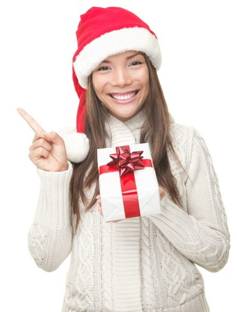 Christmas woman pointing up to the side at copy space. Isolated on white background. Beautiful young smiling woman in Santa hat and sweater showing empty copyspace. Asian  Caucasian female model. photo