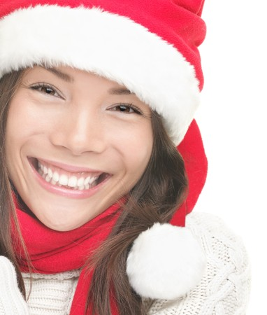 Christmas woman smiling portrait. Young woman wearing Santa hat, sweater and red scarf. Closeup photo of cute Asian  Caucasian woman isolated on white background photo