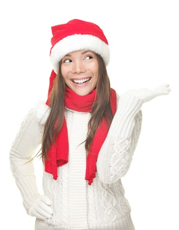 Christmas woman showing copy space looking sideways with open hand palm with room for product or text. Santa girl smiling wearing sweater, scarf and red Santa hat. Beautiful happy Caucasian  Asian woman isolated on white background. photo