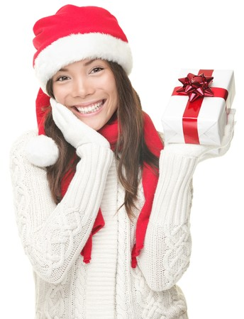 Christmas woman holding gift wearing Santa hat. Christmas woman portrait of a cute, beautiful smiling mixed Asian  Caucasian model. Isolated on white background.  photo