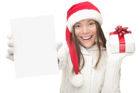advertise: Christmas woman showing blank sign with empty copy space. Beautiful young smiling woman in Santa hat holding white paper card sign. Caucasian  Asian model isolated on white background. Shallow DOF, focus on card. Stock Photo