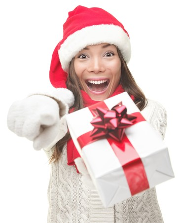 Christmas woman holding / giving gift excited pointing. Happy smiling woman in santa hat giving you a present being joyful, fresh and cheerful. Asian / Caucasian model isolated on white background. Stock Photo - 7869940