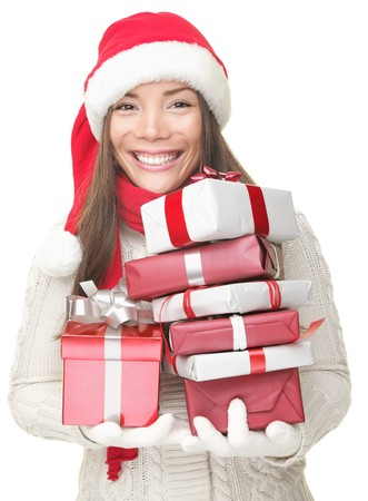 Christmas woman holding gifts wearing Santa hat. Smiling woman portrait of a beautiful mixed Asian  Caucasian model. Isolated on white background.  photo