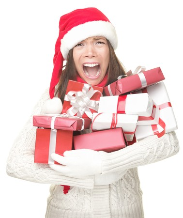 gastos: Christmas holidays shopping woman stress. Shopper holding christmas gifts stressed, frustrated and screaming angry. Funny image of Asian  caucasian woman in santa hat and arms full of gifts. Isolated on white background.