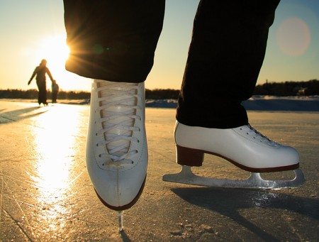 wintersports: Ice skating. Ice skates in action closeup outdoors. Classic figure ice skates on frozen lake outdoors in evening light, Mom and daughter silhouette in the background. Lac Beauport, Quebec City, Canada. Stock Photo